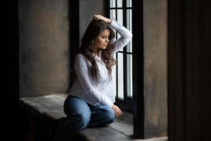 Frau in Jeans sitzt und schaut aus dem Fenster foto