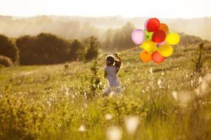 Mädchen rennt mit aufblasbaren Bällen über das Feld foto