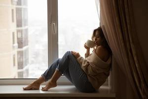 Frau am Fenster trinkt Kaffee foto
