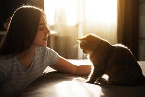Mädchen streichelt ihre geliebte rote Katze foto