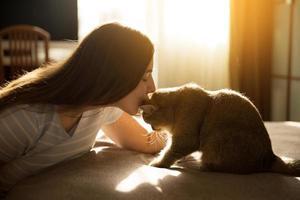 Frau küsst ihre geliebte rote Katze foto