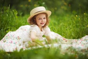 kleines glückliches Mädchen sitzt und ruht sich aus foto