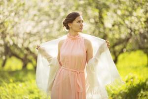 Mädchen in Kleid und Schal im Apfelgarten foto