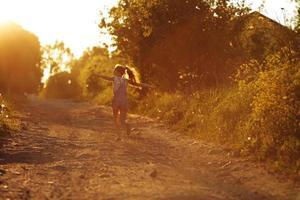glückliches kleines Mädchen, das entlang einer Landstraße läuft foto