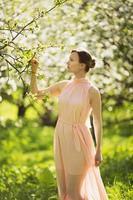 Frau steht in der Nähe eines blühenden Apfelbaums foto