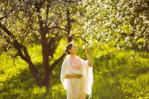 glückliche junge Frau, die einen Blumenapfel riecht foto