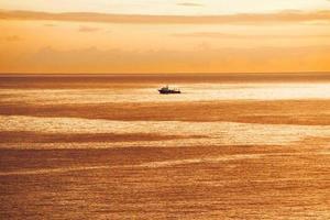 Schiff segelt bei Sonnenaufgang im Meer foto