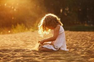 glückliches Mädchen, das im Sand spielt foto