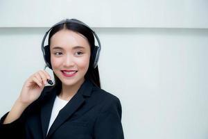 Lächelnder Kundenservice der jungen Asiatin, der über Kopfhörer spricht. foto