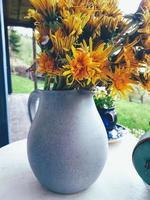 Wilde frische Blumen in Porzellankrug, alte Uhr, auf weißem Holzstuhl, grünem Gras und blauem Himmelshintergrund. Tageslicht, harte Schatten. Stillleben im rustikalen Stil. Landschaftslebensstilkonzept foto