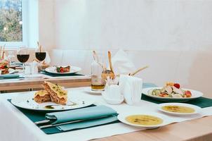 schönes Esszimmer mit Wein- und Wassergläsern, Besteck in grünen Servietten, Essen auf weißen Tellern, arrangiert vom Catering-Service in einem modernen hellen Restaurant, Café. italienische europäische küche foto