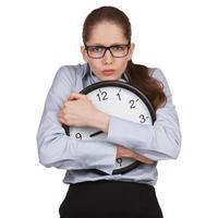 traurige Frau mit Uhr in den Händen foto