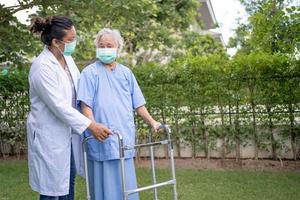 Hilfe und Pflege asiatische ältere Frau verwendet Gehhilfe mit starker Gesundheit foto