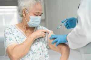 Ältere asiatische Seniorin, die gegen Covid-19 oder Coronavirus-Impfstoff erhält foto