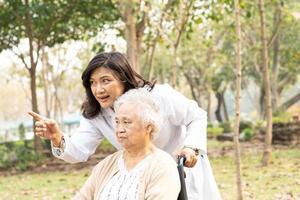 Arzt hilft asiatischer Seniorin, die im Rollstuhl sitzt foto