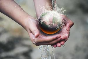 Hand hält die schwelende Kugel unter strömendem Wasser foto