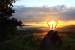 Hand hält eine Glühbirne bei Sonnenuntergang foto