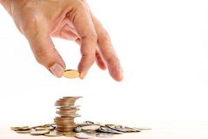 Nahaufnahme der menschlichen Hand, die eine Münze auf einen Haufen Münzen setzt. foto