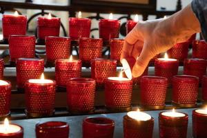Anzünden einer roten Opferkerze in einer christlichen Kirche foto