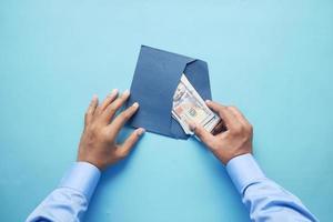 Personenhand, die Bargeld in einen Umschlag steckt, Ansicht von oben foto