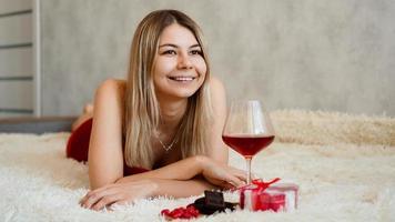 eine schöne lächelnde Blondine liegt im Bett. Valentinstag Morgen foto