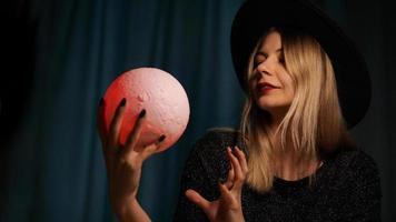 Eine junge Wahrsagerin mit Hut hält einen magischen Ball. foto