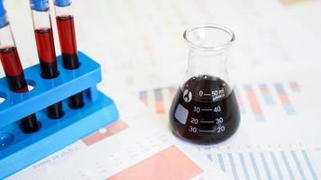 Reagenzgläser auf einem Ständer und eine Flasche mit rotem Blut foto