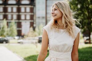 eine junge Blondine in einem weißen Kleid vor dem Hintergrund einer europäischen Stadt foto