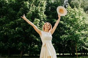 schöne junge Frau mit Strohhut und weißem Kleid in einem grünen Park foto