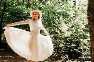 junge Frau mit Strohhut, die den Saum ihres weißen Kleides hält foto
