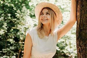 Schönes Mädchen mit Strohhut und stilvoller Kleidung steht in der Nähe eines Baumes foto