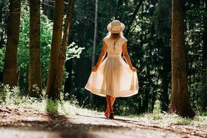 eine junge Frau in weißem Kleid und Strohhut spaziert durch den Wald foto