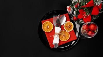 Einstellung für festliches Weihnachtsessen auf schwarzem Tisch mit Dekoration foto