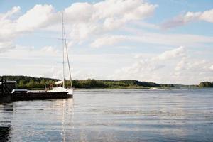 Yacht auf blauem friedlichem See auf grünem Wald und blauem Himmelshintergrund foto