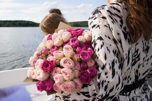 ein junges Mädchen mit einem Strauß leuchtender Blumen auf einem Kreuzfahrtschiff foto