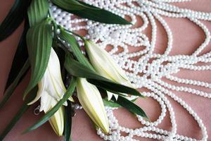 weiße Lilien und eine Perlenkette auf rosa Hintergrund. foto