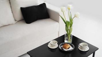 Sofa in einem modernen Interieur. auf dem Tisch liegt ein Strauß Tulpen foto