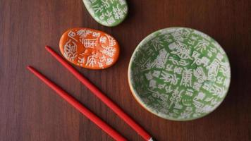 Set aus Keramikgeschirr und roten Sushi-Sticks auf Holzuntergrund foto