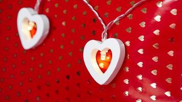 Girlande aus Holzherzen auf rotem Grund. Valentinstag foto