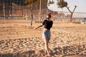 Porträt einer attraktiven Frau in der Nähe des Volleyballnetzes am Strand foto