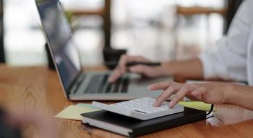 Nahaufnahme Geschäftsmann mit Taschenrechner und Laptop zum Berechnen foto