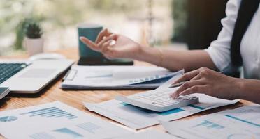 Geschäftsmann mit Taschenrechner und Laptop zum Berechnen von Finanzen foto