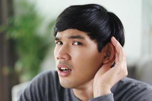 Gehörloser behinderter Mann mit Hörproblemen hält seine Hand über das Ohr. foto