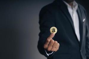 Investor Geschäftsmann hält einen goldenen Bitcoin auf dunklem Hintergrund. foto