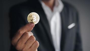 Geschäftsmann mit einem goldenen Bitcoin auf dunklem Hintergrund, Handel. foto