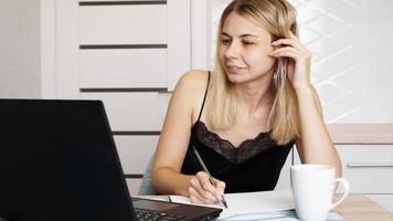 Unternehmer oder Student, der zu Hause arbeitet oder studiert und Notizen schreibt foto