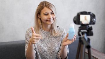 Blogger zeigt Lotion für die Haut. fröhliche Bloggerin, die Video aufnimmt foto