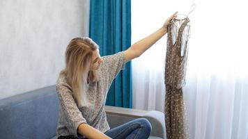 hübsche Frau hält einen Kleiderbügel mit einem Kleid foto