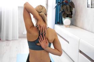 Frau, die ihren Rücken streckt - aus ihren Händen hinter ihrem Rücken sperren foto