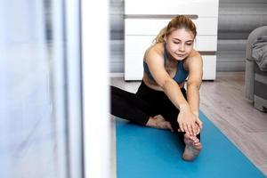 Sport-, Trainings- und Lifestyle-Konzept - Frau, die Bein auf Matte ausdehnt foto